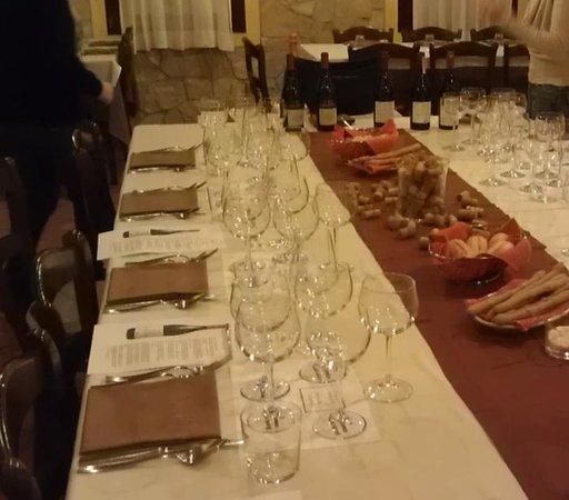 Trattoria Al Moraro: tavola imbandita, vini sullo sfondo pronti ad essere protagonisti..