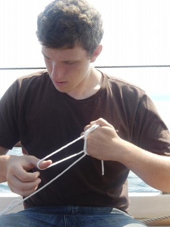 Superior Odyssey Sailing Charters: First Mate Cyrus making a nautical bracelet