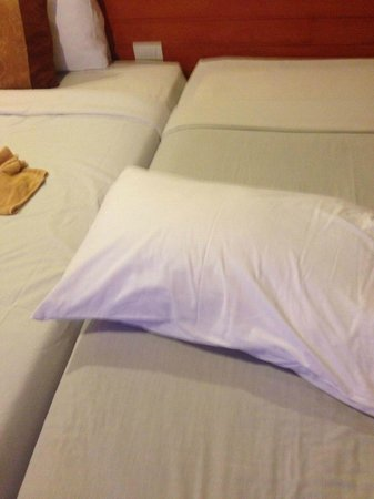 Tanawit Condotel : White pillow on the greying white sheets