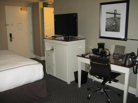 Hotel Zoe San Francisco: Desk, tv, mini bar/fridge. Bathroom area where light is on.