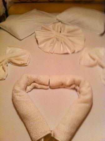 Sunset Hotel and Villas: disposizione degli asciugamani sul letto