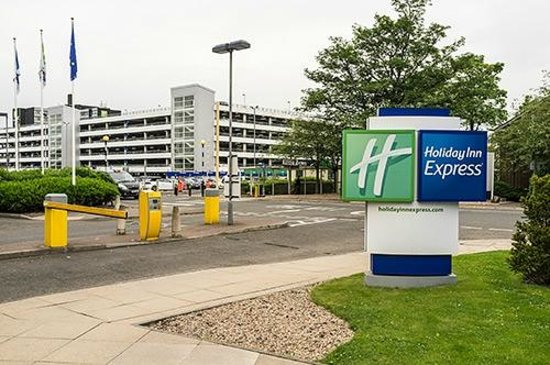 Holiday Inn Express Glasgow Airport: View from hotel towards airport, the covered walkway is far side of road just left of 'H' sign