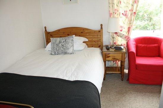 Dunedin Guest House : Bedroom with a comfy red chair