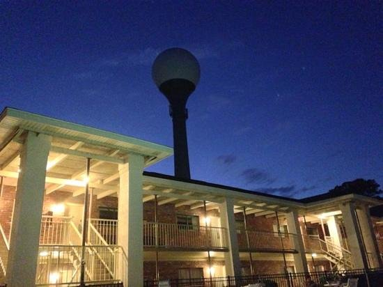 Quality Inn & Suites: the hotel and golf ball water tower at night.