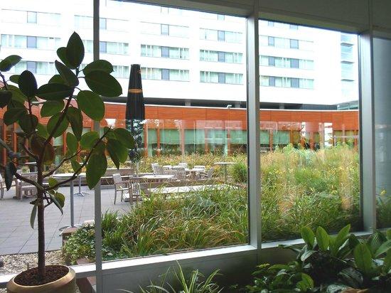 Steigenberger Airport Hotel Amsterdam: Blick von der Hotelhalle auf Gartenbereich und Speisesaal
