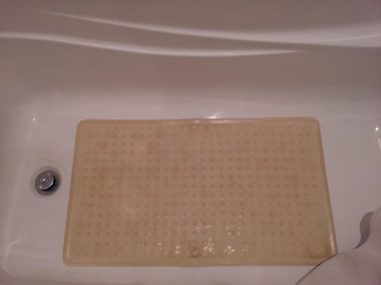 "Cracked and stained bath mat provided ""for your safety"" at Hotel Ruby Foo's."