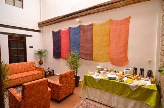 Casa de las Rosas: Comfortable den area with breakfast buffet table