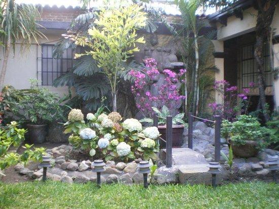 Hotel Las Camelias Inn: Flower garden with a little bridge