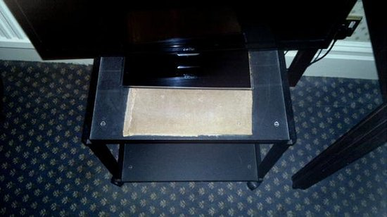 The Grand Hotel: TV stand with torn hardboard screwed over the top.