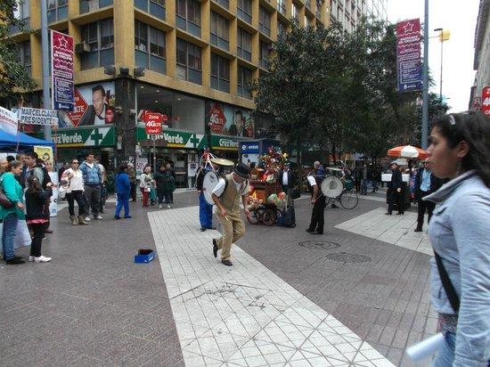Paseo Huerfanos : Santiago de Chile. Paseo Huérfanos con Paseo Ahumada. Organillero y Chinchineros bailando.