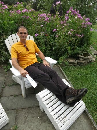 WhistleWood Farm Bed and Breakfast: My husband relaxing in the Adirondack chairs outside