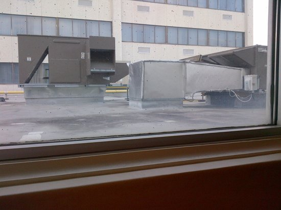 "Days Inn & Conference Centre - Timmins : The view from my ""half"" window.  Note the unknown black stuff on the windows."