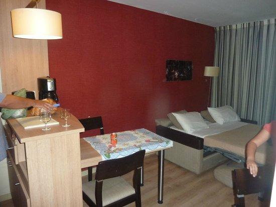 Appart'City Confort Marne la Vallee - Val d'Europe : parte de la cocina, salón y sofá-cama