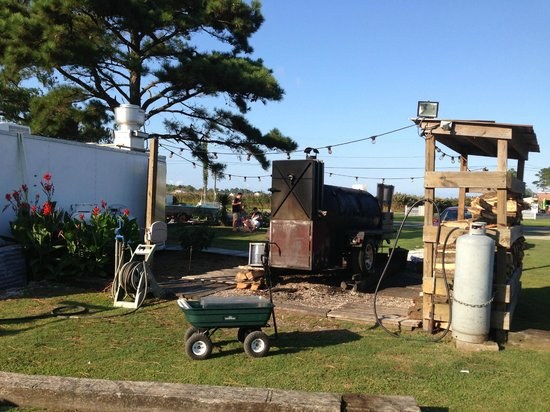Woody's Beach BBQ and Eatery: Pictre of the smoker (center) and woodpile (right)