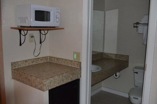 Motel 6 Tampa - Fairgrounds: Microwave and mini refrigerator with bath in background.