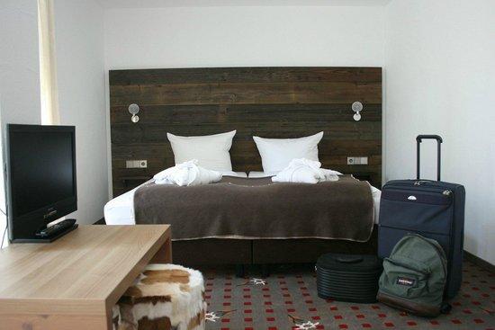 Alpin Lifestyle Lowen & Strauss: Alte Holzbohlen an der Wand vor dem Bett