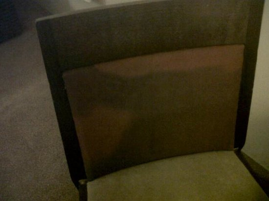 Ramada Glasgow Airport: Chair in the bedroom - this is not a shadow but filthy stains.