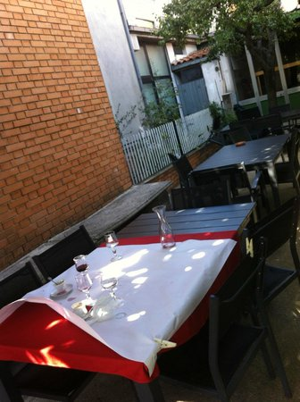 Ristorante Trattoria Il caminetto: tavoli all'aperto sotto la fresca ombra del caco e del pero