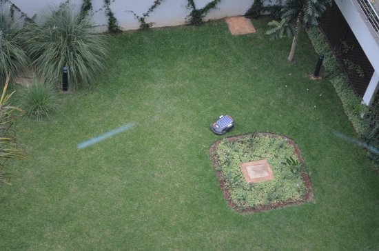 The Boma Nairobi: Robot mower on the grounds below the room