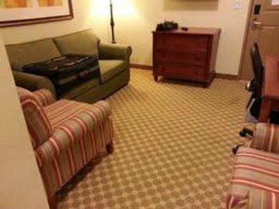 Country Inn & Suites By Carlson, Manchester Airport: Living room with sleep sofa and TV (above dresser)