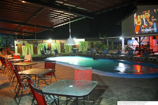 El Faro Beach Hostel: Common area tables and swimming pool watching movies