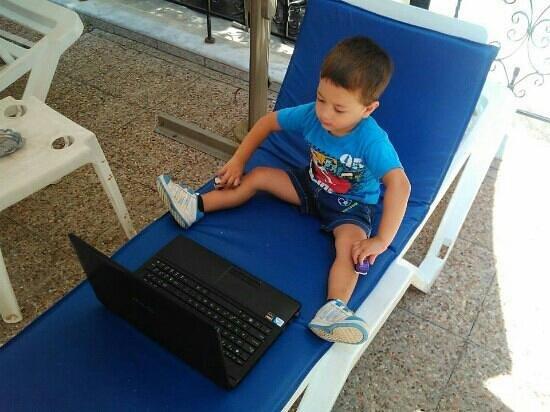 Hanioti Grand Victoria: Damir by the pool watching cartoons