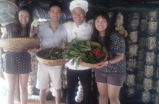 Happy with full basket of ingredients after pick up in HCM Cooking class Garden