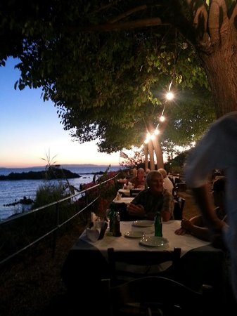 Stoupa Restaurant: Looking across the tables by the sea just after sunset
