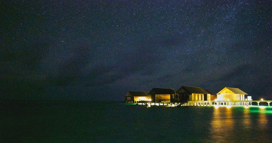 Gangehi Island Resort: The pier with over water luxury rooms and the a la carte restaurant at night.