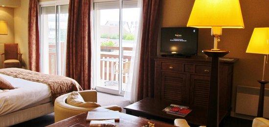 Hôtel Le Trophée : chambre salon deluxe piscine