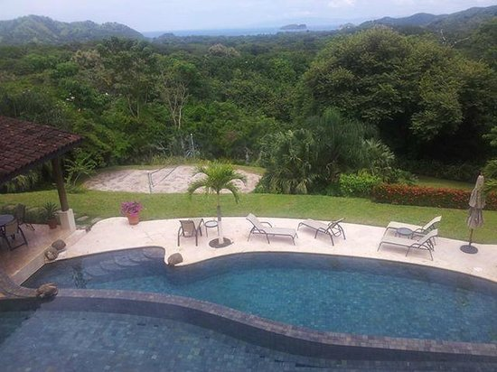 Villa Buena Onda: View of the pool and volleyball court from our ocean view room
