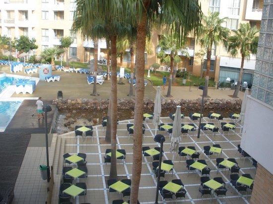 Hotel Neptuno: Vista a la zona de cafeteria de la piscina con su chirimguito al lado y dónde hacian la animació