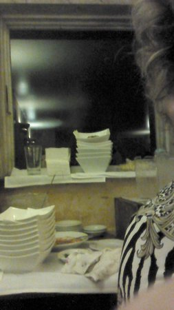Trattoria La Siciliana : The table behind me with clean and dirty plates stacked nexy to each other, nexy to the bread an