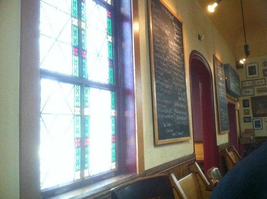 Clarkston Union Bar & Kitchen: Chalk board beer list next to the stain glass window