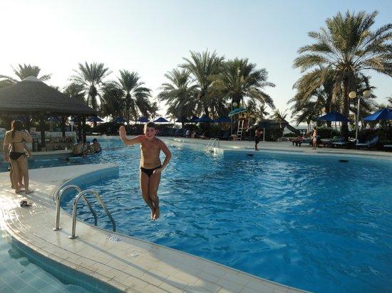 Dubai, Verenigde Arabische Emiraten: сын прыгает в бассейн с морской водой при отели
