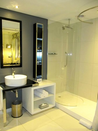 Protea Hotel Fire & Ice Johannesburg Melrose Arch: bath within room, with glass wall and a curtain to pull for privacy