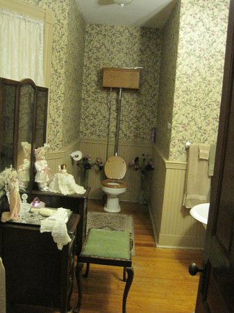 Hollerstown Hill: Bathroom with vanity decorations and worn, dirty bench fabric.