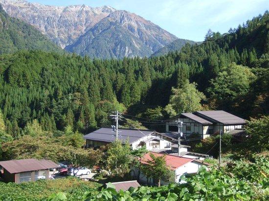 Ryokan Yakenoyu : 宿の上手にある足あらいの湯から見た宿の全景と北アルプス