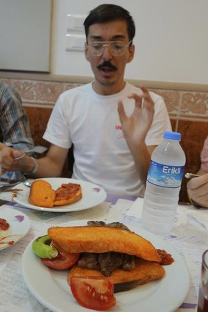 Culinary Backstreets -Tours: Tour guide Angelis with plate of turkish meatballs on bread soaked in marrow