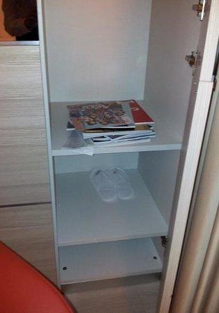 AS Hotel Limbiate Fiera: Ciabatte usate e riviste sparpagliate in un armadio della suite.