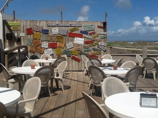Wanna-Wanna Beach Bar & Grill : Patio tables facing the beach and the cute sayings signs!