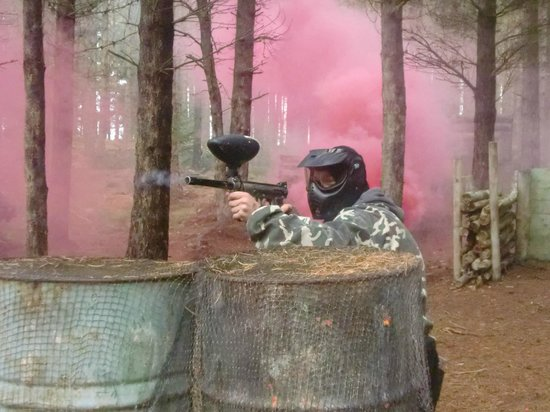 Tazball Paintball & Lazer Combat Arena: Returning fire from behind a set of metal drums.