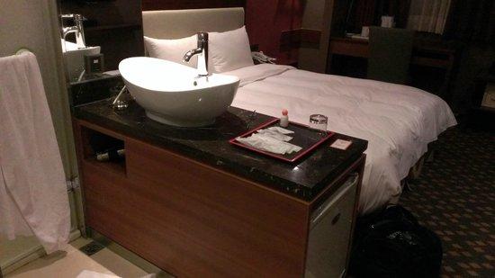 Orange Hotel-Linsen, Taipei: 洗面台がベッドの脇に。シャワー・トイレも、ワンルームの一部みたいな感じ。