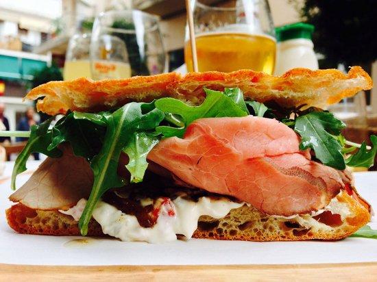 ROASBEEF...sándwich de pan de coca, roastbeef, cebolla confitada, rucula, salsa el santo y aceit