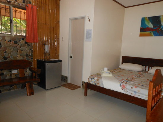 Jungle Flower Guest House: deluxe with the king bed, sofa, stone wall and refrig