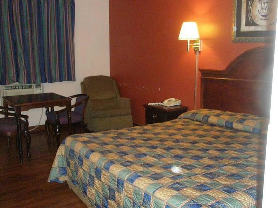 Rodeway Inn Benton Harbor: Bed, desk, chair. Spot on bedding is from camera lense, spots on wall are missing paint
