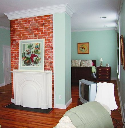 Egg & I Bed and Breakfast : Queen-size bed behind fireplace divider