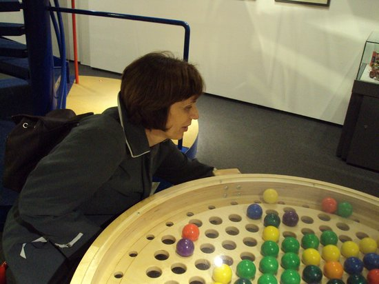 Nürnberger Spielzeugmuseum: trying to put the balls in the proper holes with fingers only