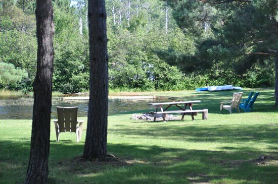 Algonquin's Edge Resort : view of public area fire pit, swimming and relax spot from house trailer cottage