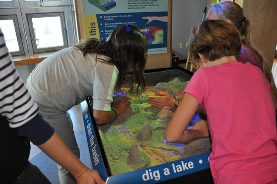 ECHO Leahy Center for Lake Champlain: ECHO guests learn about water behavior by manipulating sand in the 3D watershed table.